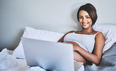 Buy stock photo Portrait of a cheerful pregnant woman lying on a bed at home relaxing while browsing on a laptop during the day