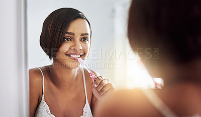 Buy stock photo Shot of an attractive young woman brushing her teeth in the bathroom