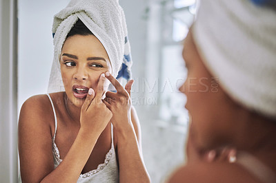 Buy stock photo Shot of an attractive young woman squeezing a pimple on her face in the bathroom