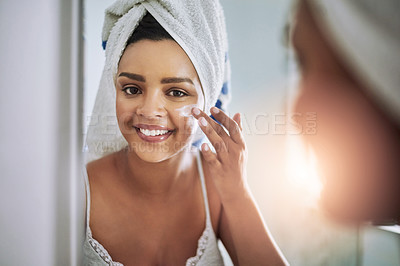 Buy stock photo Portrait of an attractive young woman applying moisturizer to her face in the bathroom