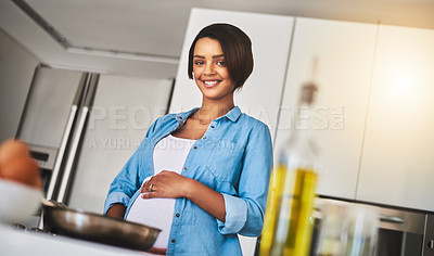 Buy stock photo Shot of a pregnant young woman preparing a meal on the stove at home