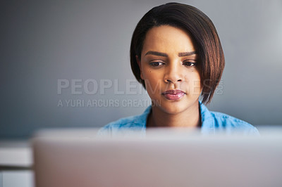 Buy stock photo Shot of an attractive young woman using a laptop at home against a gray background