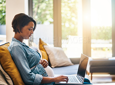 Buy stock photo Shot of a pregnant young woman using her laptop at home