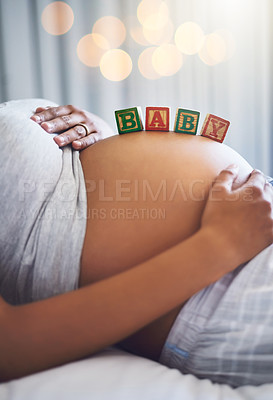 Buy stock photo Cropped shot of a pregnant woman with wooden blocks on her belly that spell the word baby