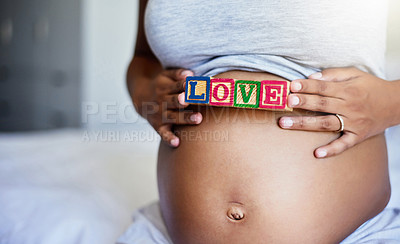 Buy stock photo Cropped shot of a pregnant woman with wooden blocks on her belly that spell the word love