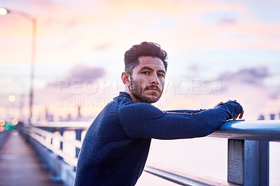 Buy stock photo Portrait of a sporty young man taking a break while exercising outdoors