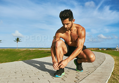 Buy stock photo Shot of a handsome young man tying his shoelaces while exercising outdoors