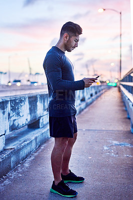 Buy stock photo Shot of a sporty young man using a cellphone outdoors