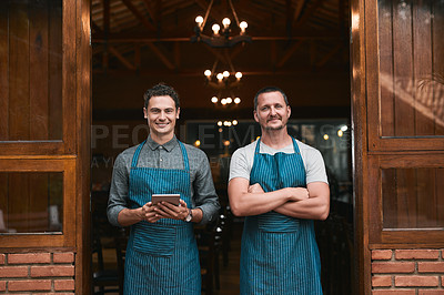 Buy stock photo Portrait of two cheerful young businessmen standing together casually in front of a beer brewery outside during the day
