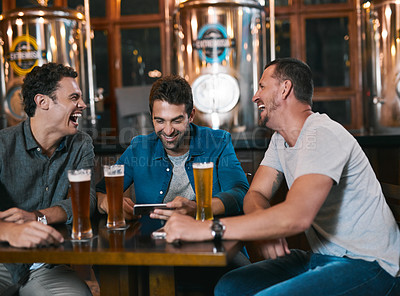 Buy stock photo Shot of three cheerful young men drinking beer together at a table inside of a beer brewery during the day