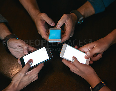 Buy stock photo High angle shot of three unrecognizable people seated in a circle at a table while browsing on their cellphones