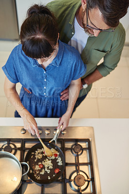 Buy stock photo High angle shot of a mature couple cooking together at home