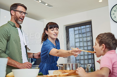 Buy stock photo Shot of a mother giving her son a taste of the meal that she's cooking at home