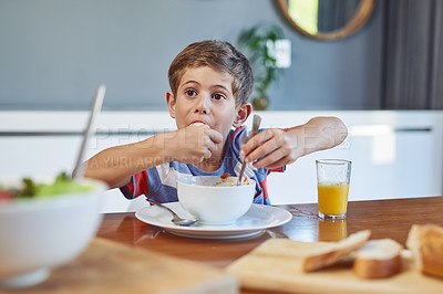 Buy stock photo Shot of an adorable little boy enjoying a meal at home