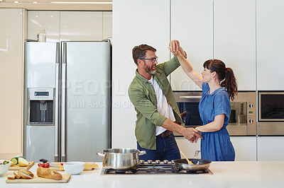 Buy stock photo Shot of a mature couple dancing while cooking together at home