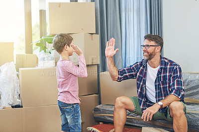Buy stock photo Shot of a happy father and son giving each other a high five on moving day