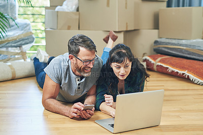 Buy stock photo Shot of a husband and wife using a laptop together on moving day
