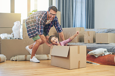 Buy stock photo Shot of a happy father and son having fun together on moving day