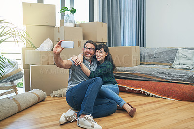 Buy stock photo Shot of a happy couple taking selfies together on moving day