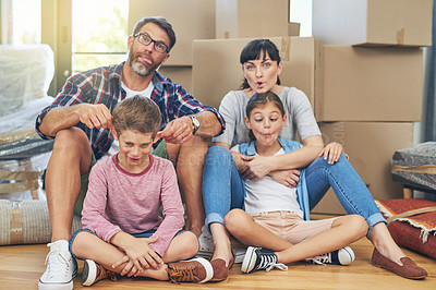Buy stock photo Portrait of a happy family making funny faces together in their home on moving day