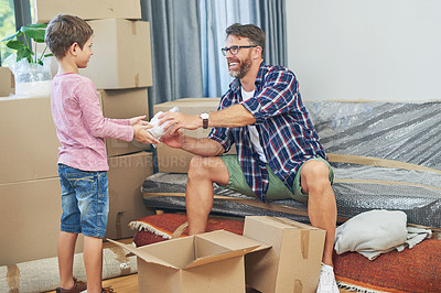 Buy stock photo Shot of an adorable little boy helping his father pack on moving day