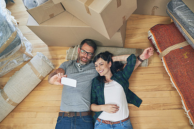 Buy stock photo High angle shot of a happy couple taking selfies together on moving day