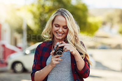 Buy stock photo Cropped shot of a young beautiful woman looking at photographs on a camera in the city