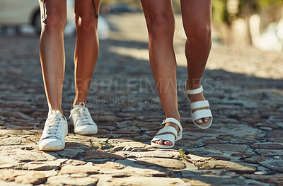 Buy stock photo Low angle shot of two unrecognizable women walking in the city