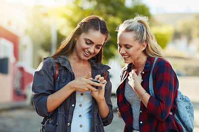Buy stock photo Cropped shot of two beautiful female friends using a cellphone together in the city