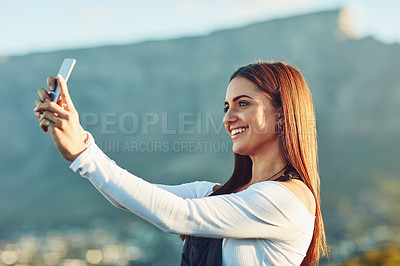 Buy stock photo Cropped shot of a beautiful young woman taking a selfie  in nature