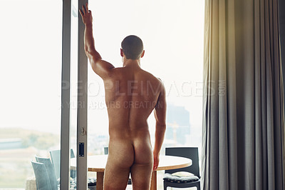 Buy stock photo Rearview shot of a naked man standing in front of a window looking out at the city at home during the day
