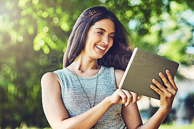 Buy stock photo Shot of an attractive young woman using a digital tablet outdoors