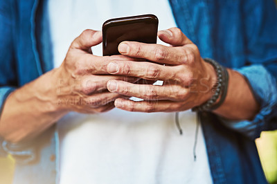 Buy stock photo Closeup shot of an unrecognizable man using a cellphone outdoors