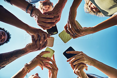 Buy stock photo Shot of a group of people using their cellphones in synchronicity outdoors