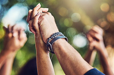 Buy stock photo Closeup shot of an unrecognizable group of people holding hands with their arms raised outdoors