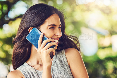 Buy stock photo Shot of an attractive young woman talking on a cellphone outdoors