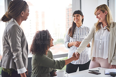 Buy stock photo Cropped shot of a group of businesswomen shaking hands in the office