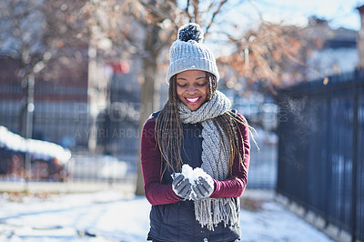 Buy stock photo Shot of a beautiful young woman holding a snowball on a wintery day outdoors