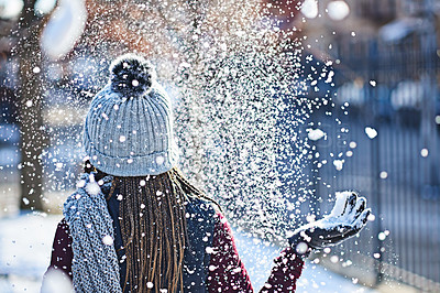 Buy stock photo Rearview shot of a young woman throwing snow on a wintery day outdoors