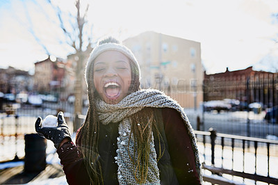 Buy stock photo Shot of a beautiful young woman throwing a snowball on a wintery day outdoors