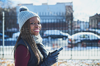Buy stock photo Shot of a beautiful young woman using a mobile phone on a snowy day outdoors