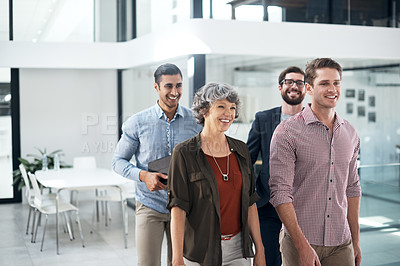 Buy stock photo Shot of a group of businesspeople walking in an office