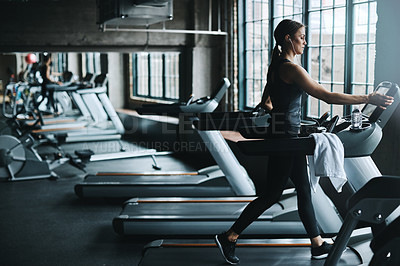 Buy stock photo Shot of an attractive young woman working out on a treadmill in a gym