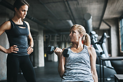 Buy stock photo Cropped shot of a mature woman lifting weights with a female instructor at the gym