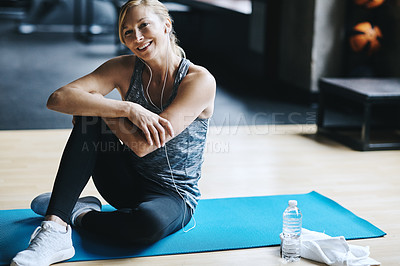 Buy stock photo Full length shot of an attractive young woman listening to music while working out in the gym