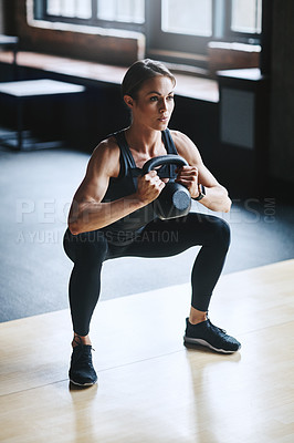 Buy stock photo Full length shot of an attractive young woman working out with a kettle bell in the gym