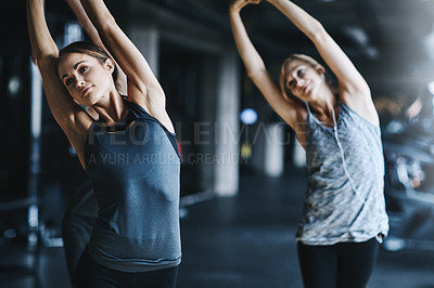 Buy stock photo Cropped shot of two attractive young women stretching before their workout in the gym