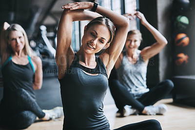 Buy stock photo Cropped shot of three attractive and athletic women stretching before their workout in the gym
