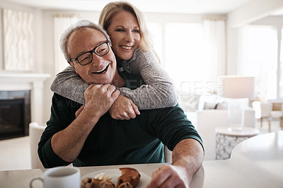 Buy stock photo Shot of an affectionate mature couple having coffee and a snack together during a relaxed day at home