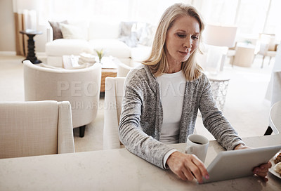 Buy stock photo Shot of a mature woman using a digital tablet while relaxing at home